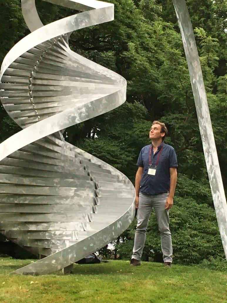 Graduate student standing next to a DNA strand sculpture